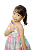 Cute Little Girl Eating Lollipop. Cute little girl eating her lollipop isolated over white background Royalty Free Stock Image