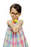 Cute Little Girl Eating Lollipop. Cute little girl wearing glasses eating her lollipop isolated over white background Royalty Free Stock Photos
