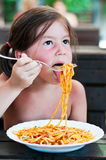 Cute little girl eating pasta. Portrait of a cute little girl eating pasta with bolognese sauce Royalty Free Stock Photo