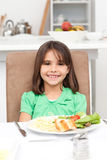 Cute little girl eating pasta and salad Royalty Free Stock Photography