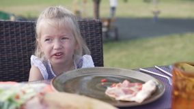 Cute little girl eating pizza in a cafe on the street stock footage