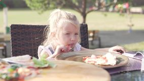 Cute little girl eating pizza in a cafe on the street on a hot summer day stock footage