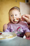 Cute little girl eating porridge Stock Image