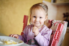 Cute little girl eating porridge Royalty Free Stock Image