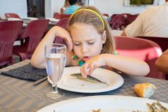 Cute little girl eating a sardine cooked in a white dish in restaurant. Portrait of five years old blonde little girl with diadem eating a sardine cooked fish royalty free stock photos