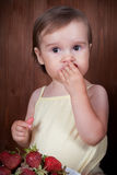 Cute little girl eating strawberries Stock Image