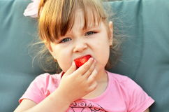 Cute little girl eating a strawberry. Child with food. Healthy eating.Close-up of young  child holding and eating fresh red strawberry fruit Stock Photo