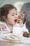 Cute little girl eating strawberry with father at breakfast table Royalty Free Stock Images