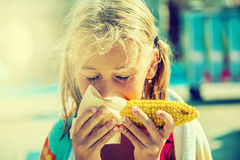 Cute little girl eating sweet corn.Toned photo Royalty Free Stock Photography