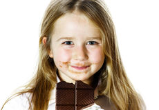 Cute little girl eating tablet of chocolate Royalty Free Stock Photos