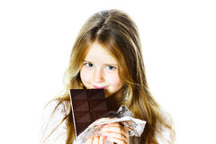 Cute little girl eating tablet of chocolate. Isolated on white background Royalty Free Stock Photos