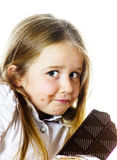 Cute little girl eating tablet of chocolate Royalty Free Stock Photo