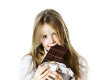 Cute little girl eating tablet of chocolate Royalty Free Stock Image