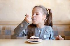 Cute little girl eating tasty cake. In kitchen stock image