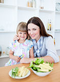 Cute little girl eating vegetables with her mother Stock Photography