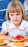 Cute little girl eating waffles with strawberries Royalty Free Stock Image