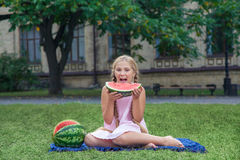 Cute little girl eating watermelon on the grass in summer time. with ponytail long hair and toothy smile sitting on grass and enjo Stock Photos