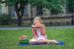 Cute little girl eating watermelon on the grass in summer time. with ponytail long hair and toothy smile sitting on grass and enjo Royalty Free Stock Images