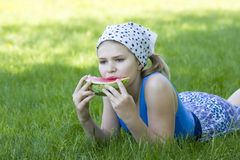Cute little girl eating watermelon on the grass Stock Photo