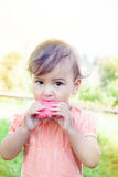 Cute little girl eating watermelon on the grass in summertime royalty free stock photo
