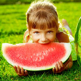Cute little girl eating watermelon and lying on the green grass Royalty Free Stock Images