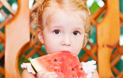 Cute little girl eating watermelon. In summertime royalty free stock images