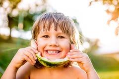 Cute little girl eating watermelon in sunny summer garden Stock Photography