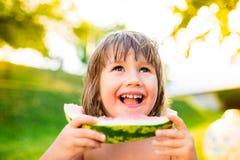 Cute little girl eating watermelon in sunny summer garden Stock Images