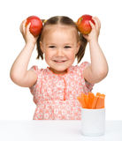 Cute little girl eats carrot and apples royalty free stock image