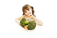 Cute little girl eats carrot and broccoli Stock Images