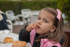 Cute little girl eats hamburger with potato sitting in cafe outd Royalty Free Stock Images