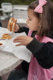 Cute little girl eats hamburger with potato sitting in cafe outd Stock Photography