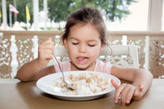 Cute little girl eats rice in a summer cafe stock image