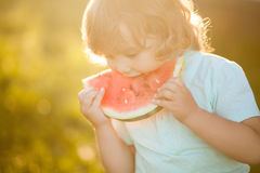 Cute little girl eats a slice of watermelon outdoors Royalty Free Stock Photos