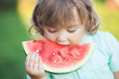 Cute little girl eats a slice of watermelon outdoors Royalty Free Stock Images