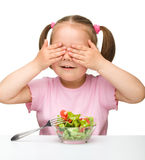 Cute little girl eats vegetable salad Royalty Free Stock Images