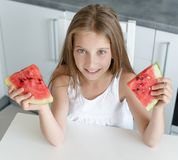 Cute little girl eats a watermelon in the kitchen Stock Photography
