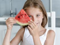 Cute little girl eats a watermelon in the kitchen Royalty Free Stock Photo