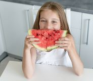 Cute little girl eats a watermelon in the kitchen Stock Image