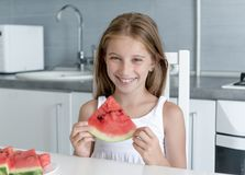 Cute little girl eats a watermelon in the kitchen Royalty Free Stock Image