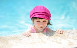 Cute little girl on the edge of swimming pool Royalty Free Stock Photography