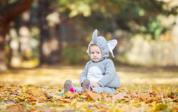 Little girl in elephant costume playing in autumn forest Royalty Free Stock Image