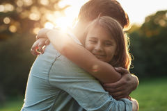 Cute little girl embracing her father on a sunny day Royalty Free Stock Images