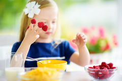 Cute little girl enjoying her breakfast at home. Pretty child eating corn flakes and raspberries and drinking milk before school. Stock Images