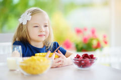 Cute little girl enjoying her breakfast at home. Pretty child eating corn flakes and raspberries and drinking milk before school. Royalty Free Stock Photo