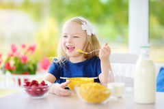 Cute little girl enjoying her breakfast at home. Pretty child eating corn flakes and raspberries and drinking milk before school. Stock Photos