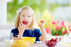 Cute little girl enjoying her breakfast at home. Pretty child eating corn flakes and raspberries and drinking milk before school. stock photography