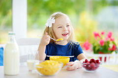Cute little girl enjoying her breakfast at home. Pretty child eating corn flakes and raspberries and drinking milk before school. royalty free stock images