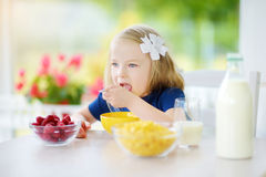 Cute little girl enjoying her breakfast at home. Pretty child eating corn flakes and raspberries and drinking milk before school. Stock Photo