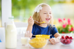 Cute little girl enjoying her breakfast at home. Pretty child eating corn flakes and raspberries and drinking milk before school. Royalty Free Stock Photos